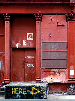 Photograph of red building with street art and graffiti