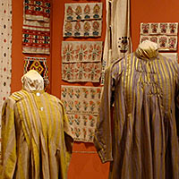 "Textiles from ""From Tent to Palace"" exhibit showing clothing and wall hangings"